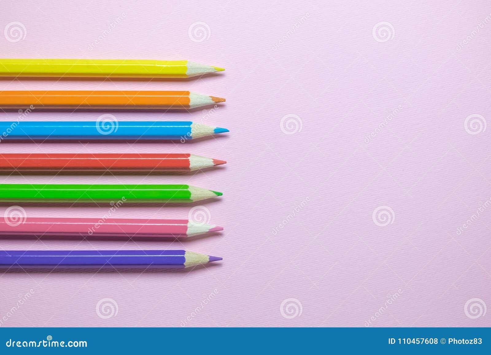 Lägenhet som är lekmanna- av träfärgpennor i olika färger på vanlig rosa bakgrund