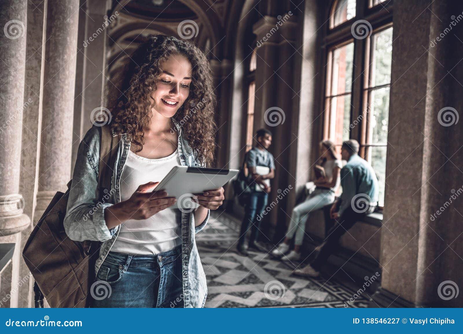 Lära online Härlig kvinnlig student som förbereder sig till kurser på den digitala minnestavlan