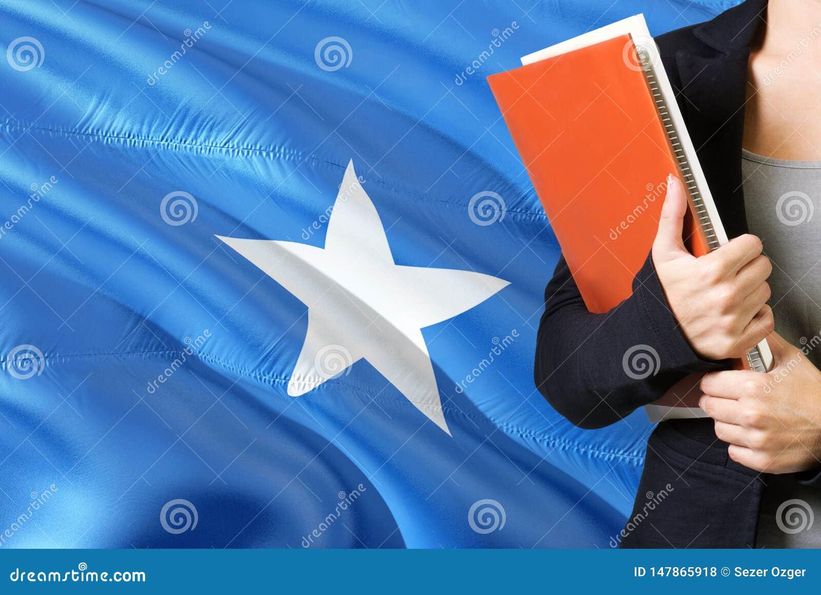 Lära Somalian språkbegrepp Anseende för ung kvinna med den Somalia flaggan i bakgrunden Lärare som rymmer böcker, apelsin