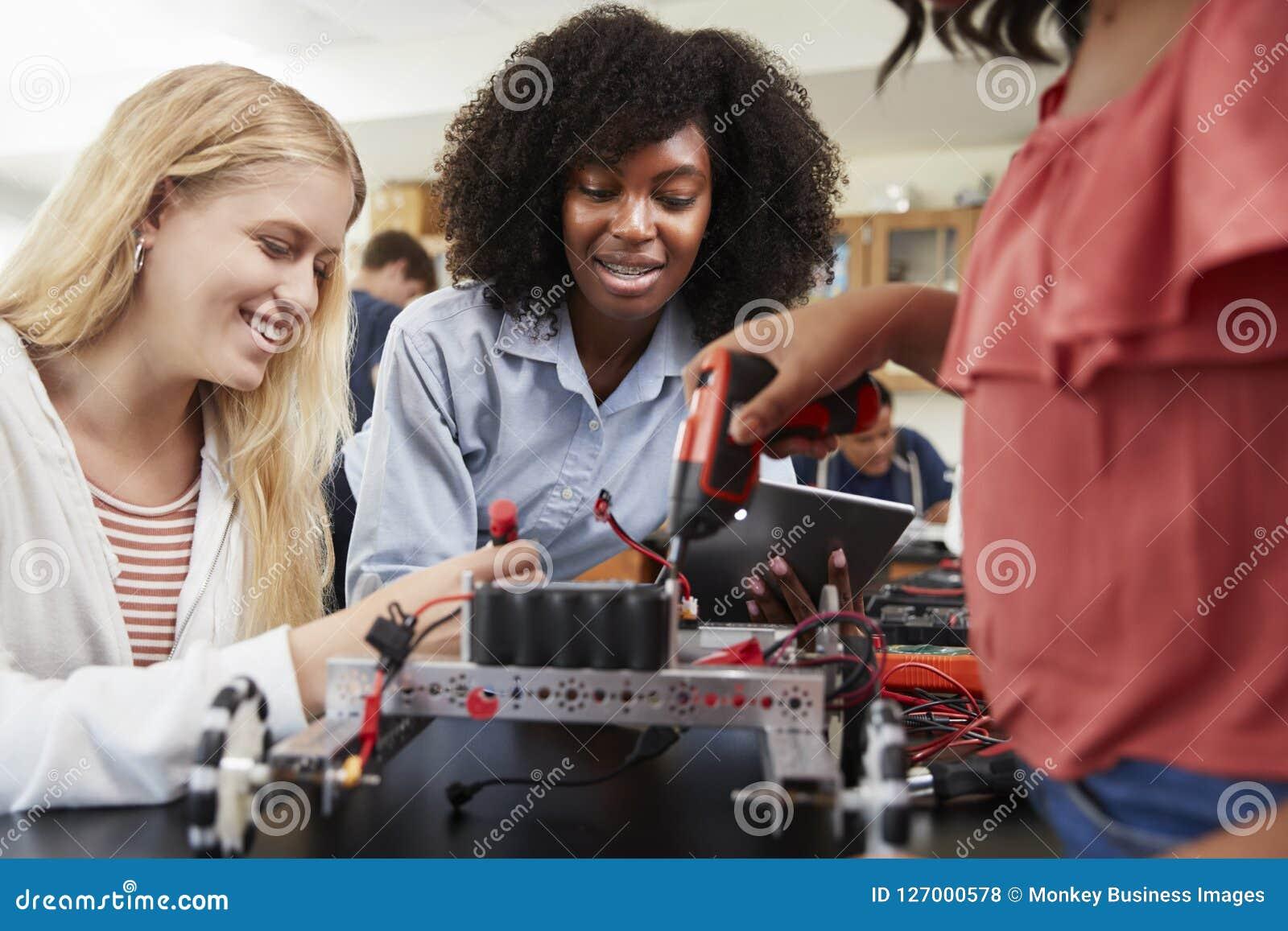 Lärare With Female Pupils som bygger det Robotic medlet i vetenskapskurs
