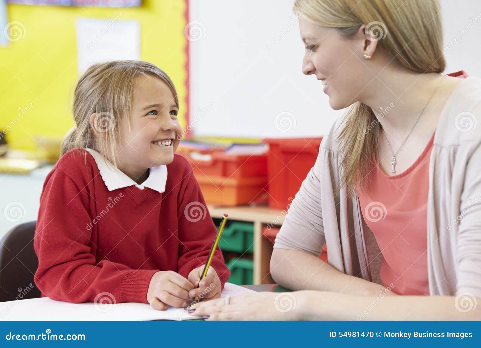 Lärare Helping Female Pupil med praktiserande handstil på skrivbordet