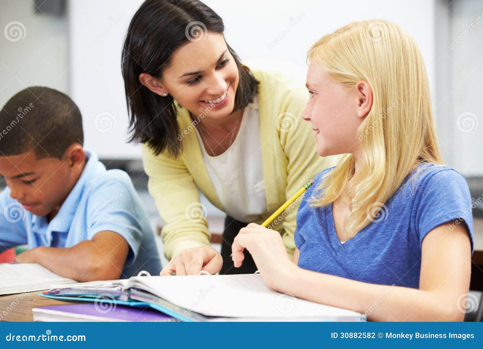 Lärare Helping Pupils Studying på skrivbord i klassrum
