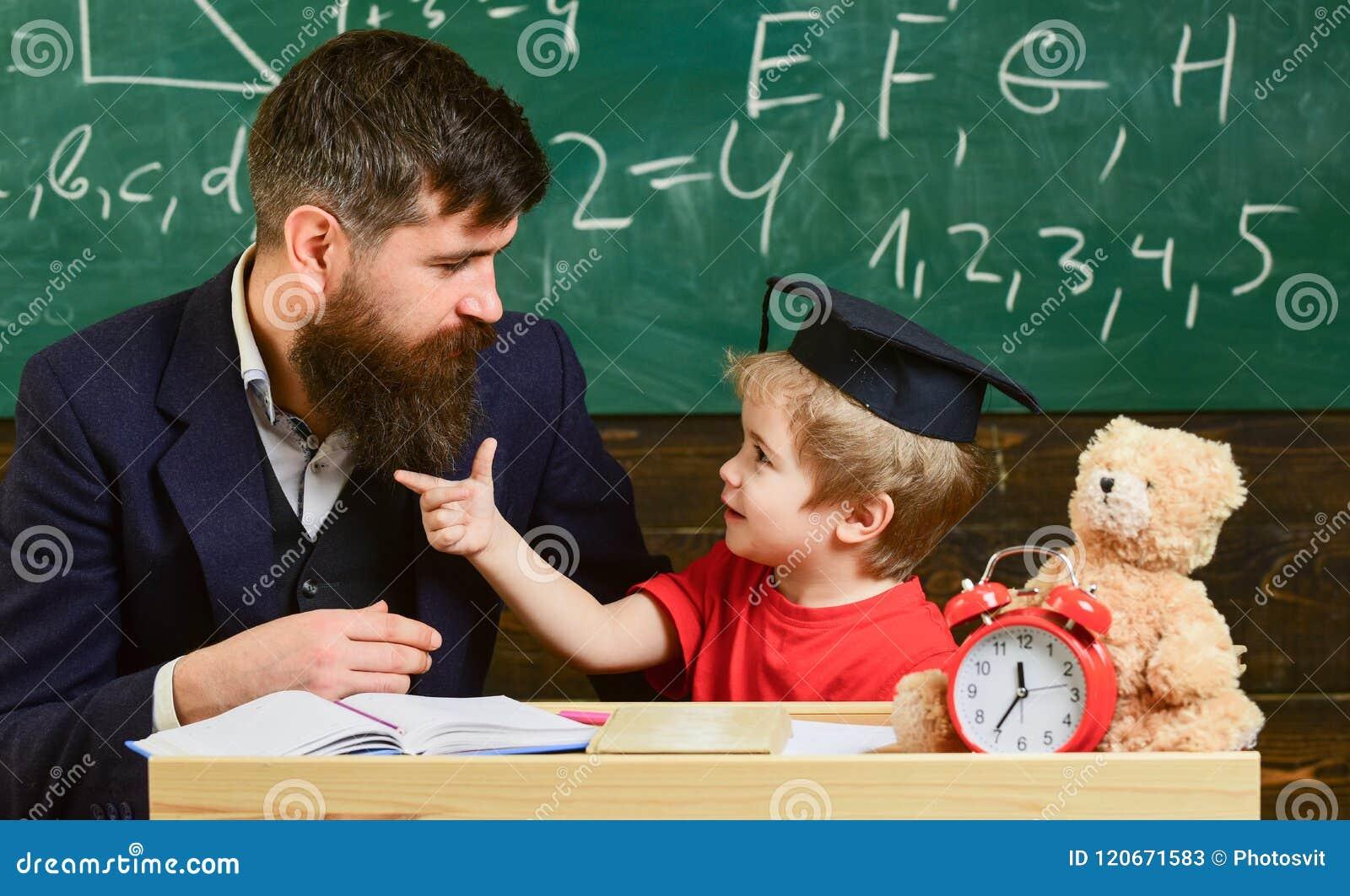 Lärare och elev i akademikermössan, svart tavla på bakgrund Styggt barnbegrepp Gladlynt distrahera för unge medan