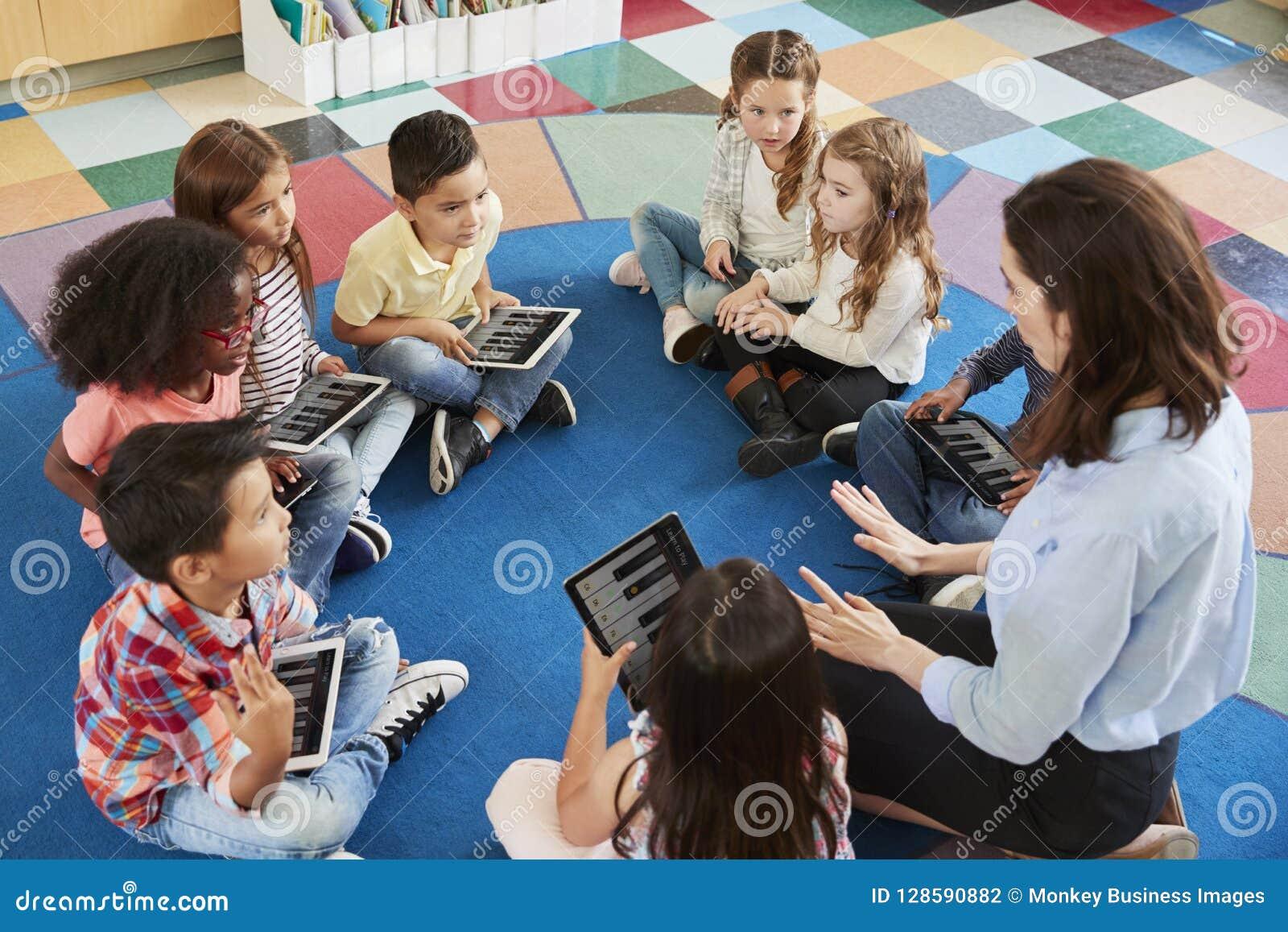 Lärare och ungar i en grundskolakurs med minnestavlor