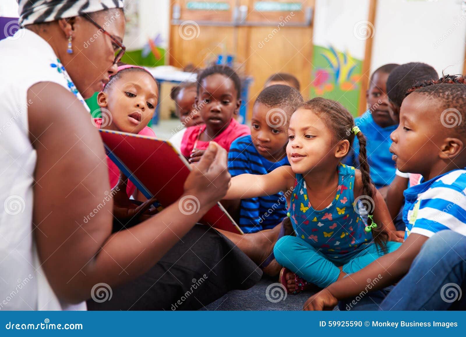 Lärare som läser en bok med en grupp av förskole- barn