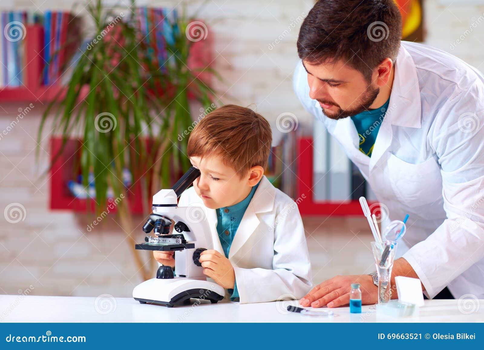 Lärarehjälpunge som för experiment med mikroskopet i skolalabb