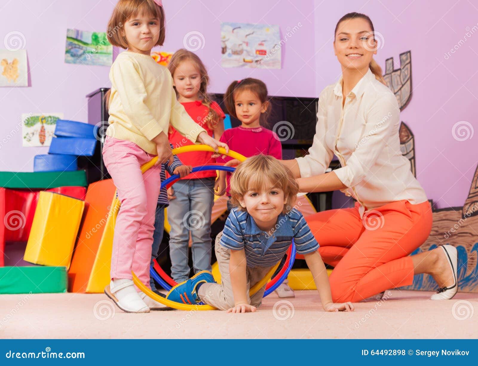 Läraren ungar i dagislek spelar med beslaget