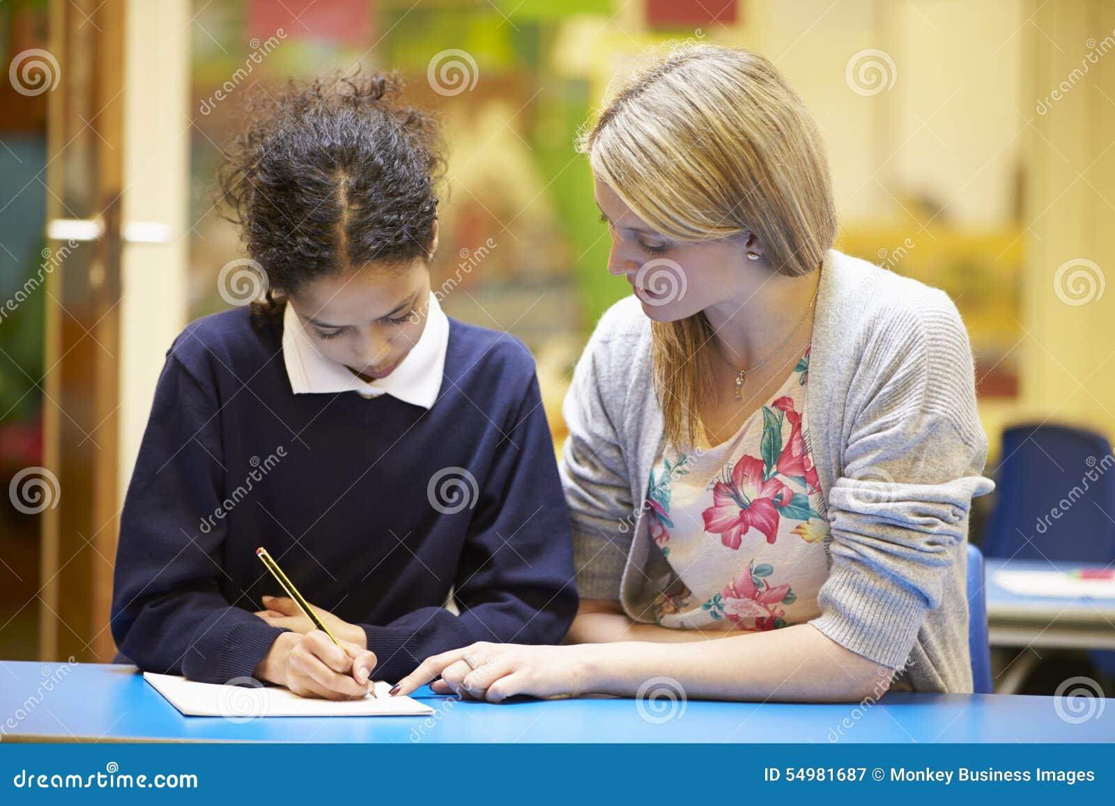 LärareWith Female Pupil läsning på skrivbordet i klassrum