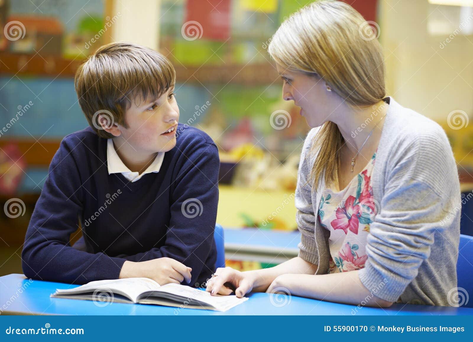 LärareWith Male Pupil läsning på skrivbordet i klassrum