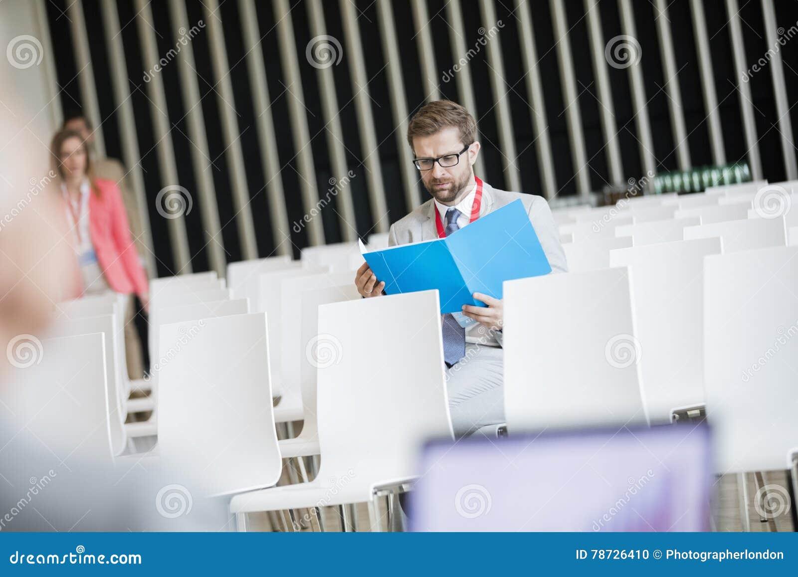 Läs- mapp för affärsman, medan sitta i seminariumkorridor på konventcentret