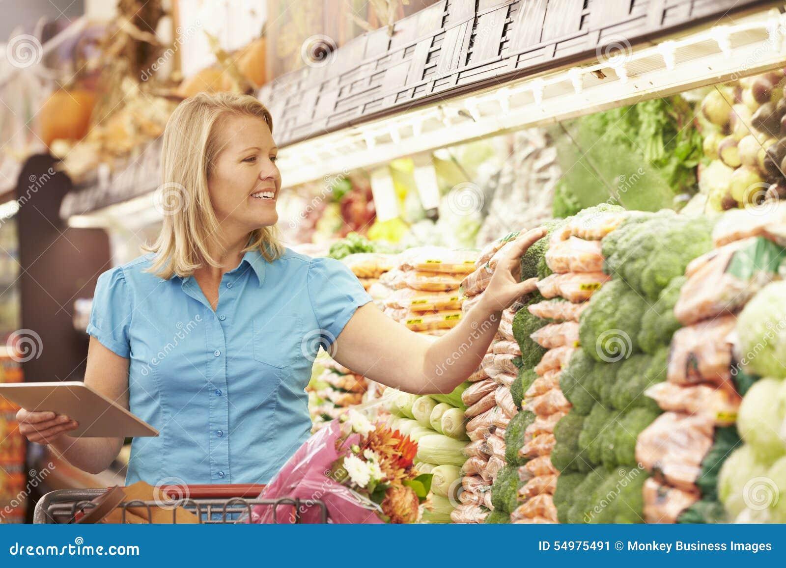 Läs- shoppinglista för kvinna från den Digital minnestavlan i supermarket