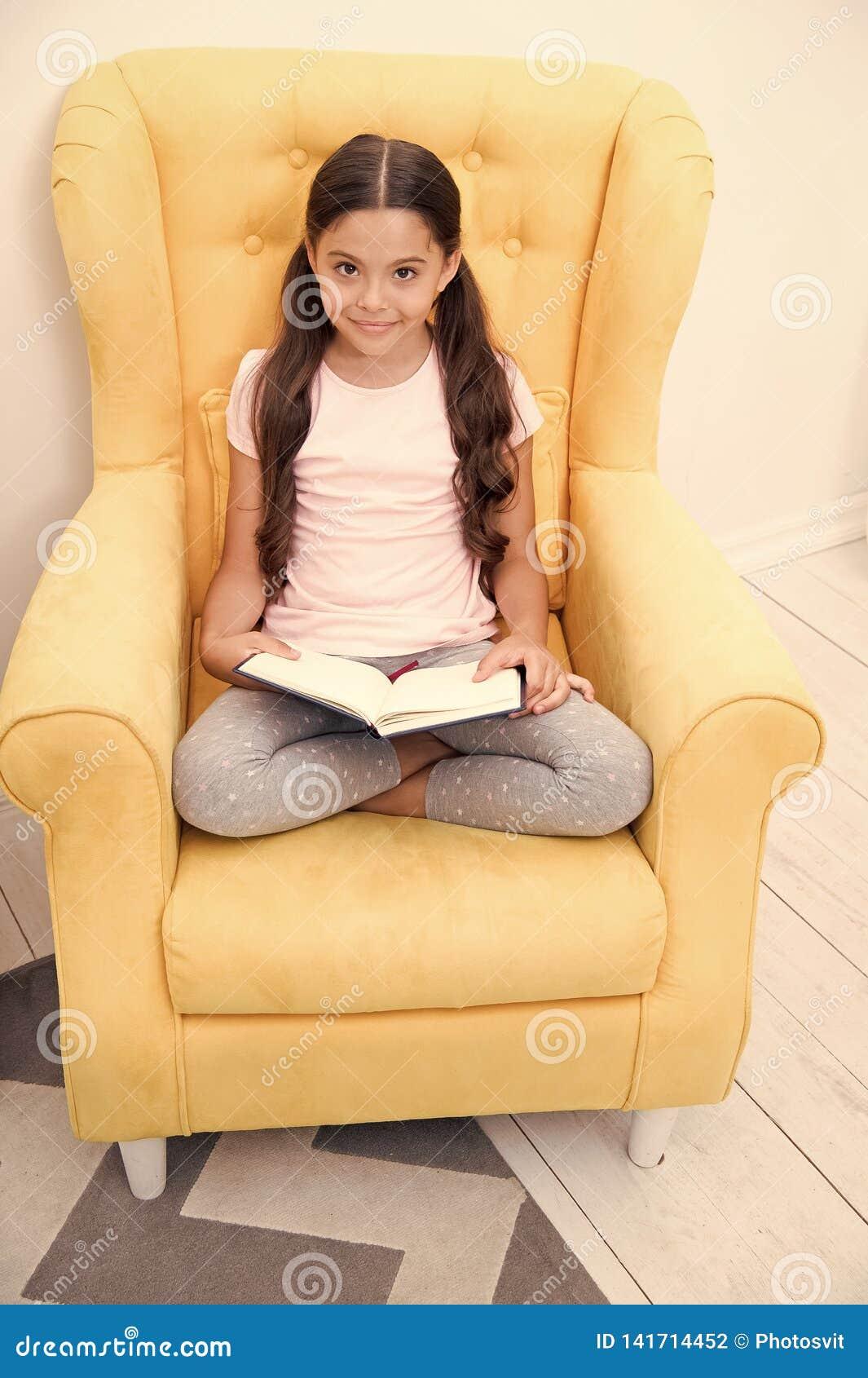 Läsa användbar hobby Flickabarnet sitter den gula fåtöljen lästa boken Gullig bokmal för unge Angenäm tid i hemtrevligt sovrum fl
