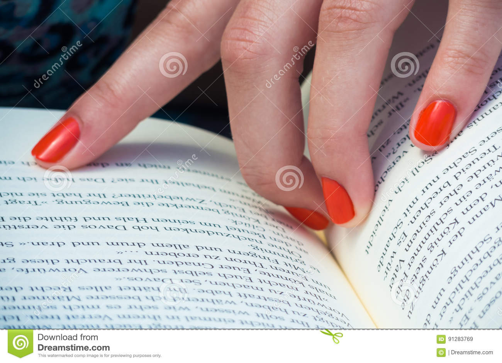Läsa en bok med det orange fingret spikar