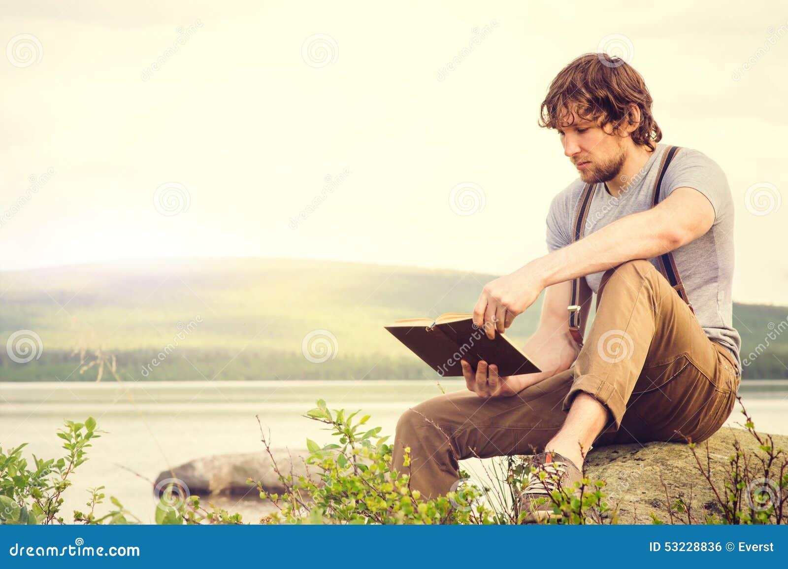 Läsebok för ung man som är utomhus- med den scandinavian sjön på bakgrund
