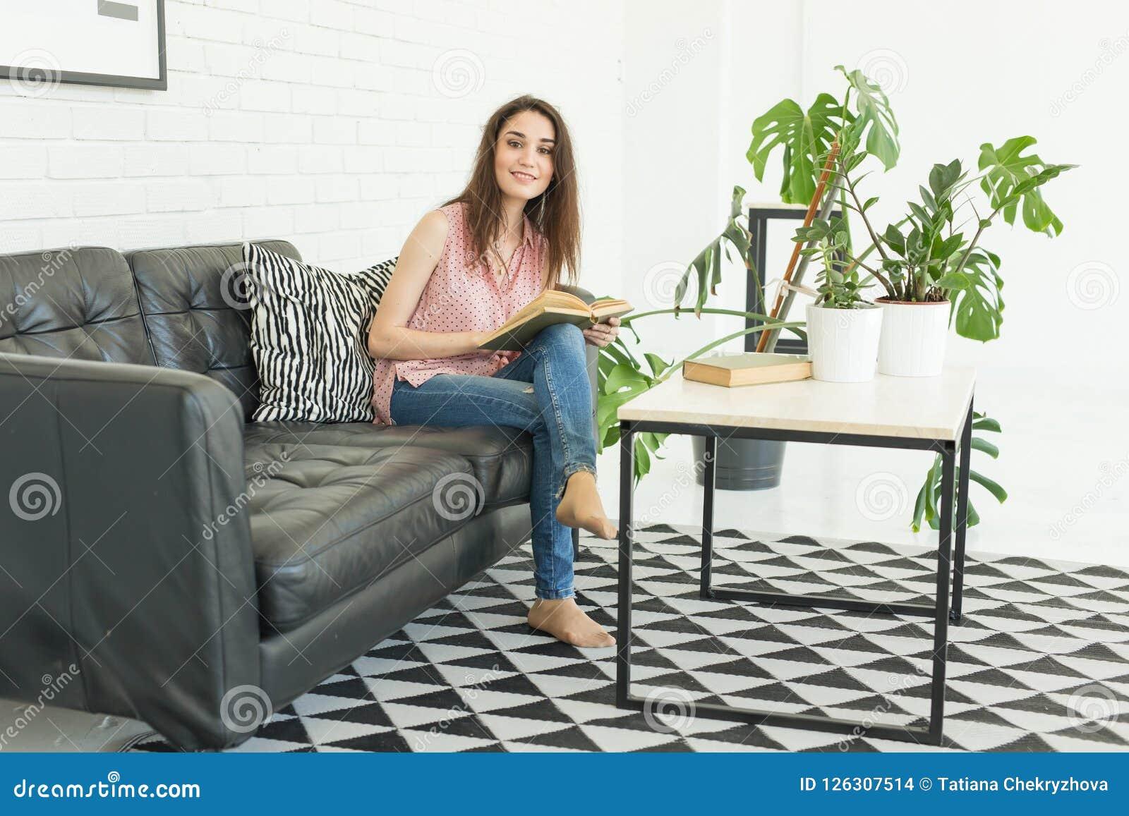 Läsning utbildning, kultur, folkbegrepp - den unga studentkvinnan läser en bok, medan hon sitter på soffan i a