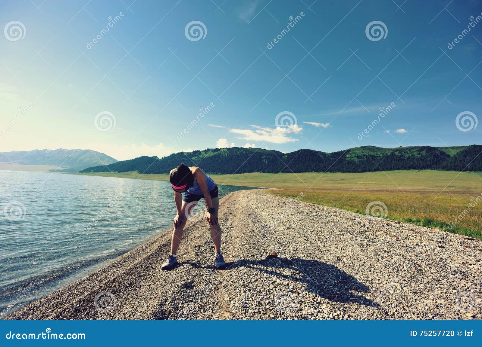 Läufer, der eine Pause macht, nachdem auf Küste stark laufen