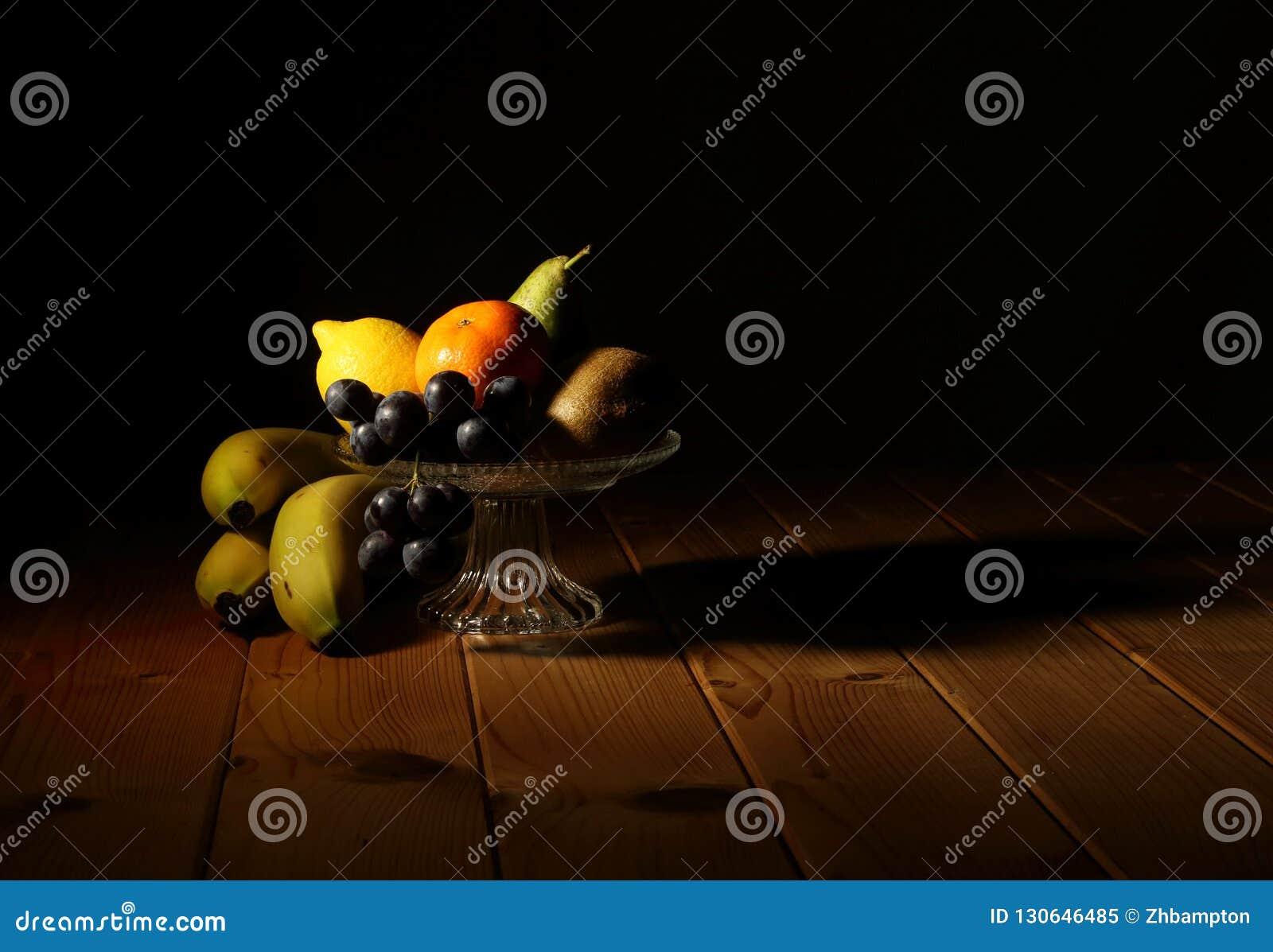 Låg nyckel- frukt i en stilleben för exponeringsglasbunke