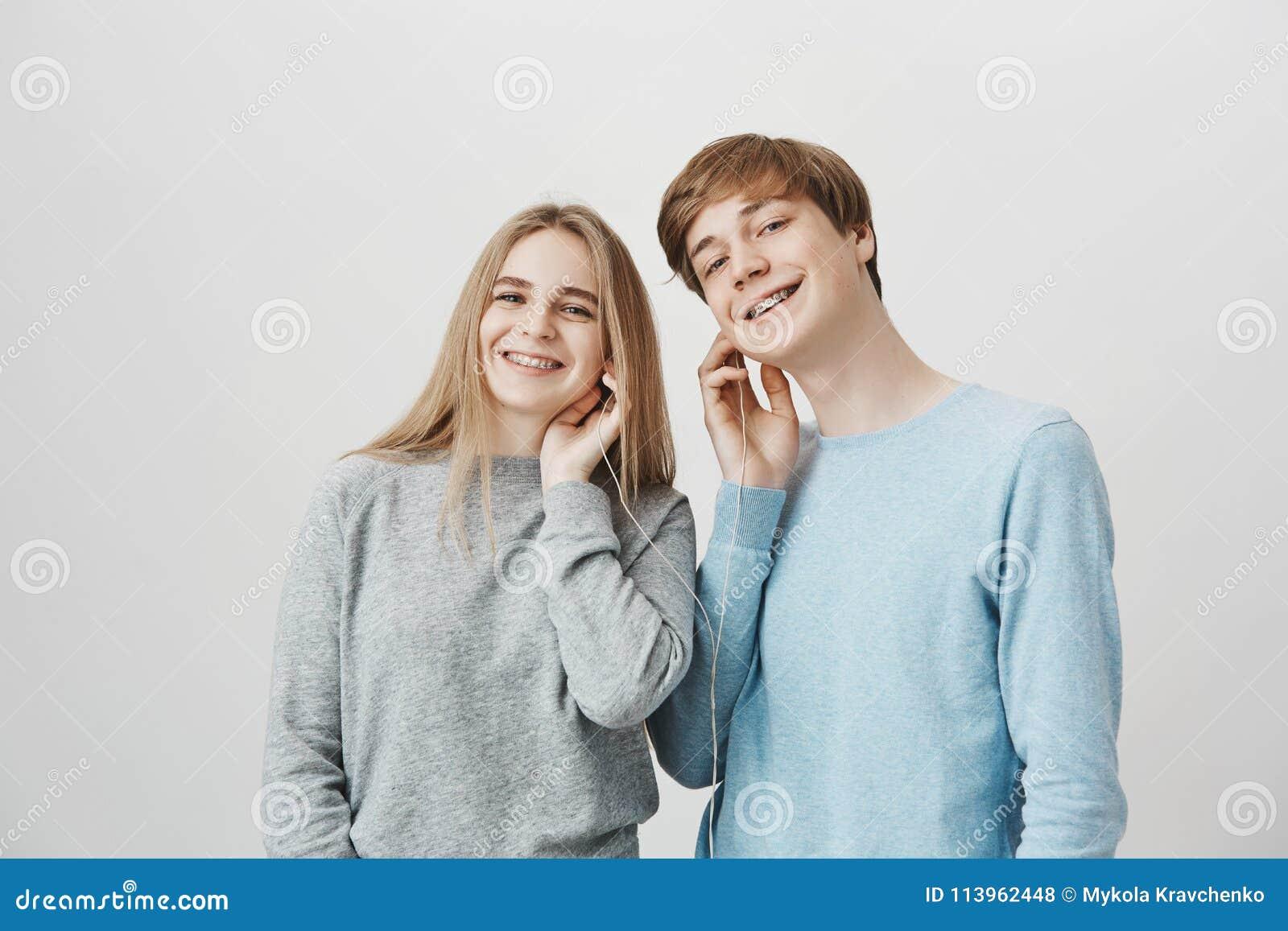 Låna mig dina öron Vänskapsmatchen tillfredsställde den snygga pojkvännen och flickvännen som delar hörlurar medan den lyssnande