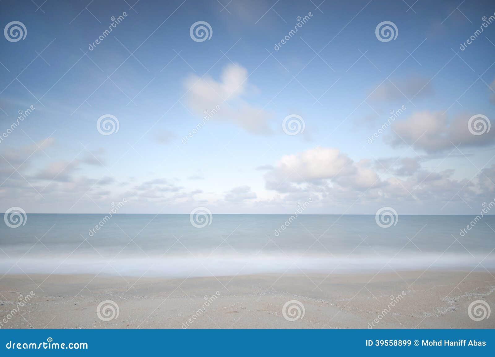 Lång exponering av stranden, vågor, blå himmel och rörelsemoln