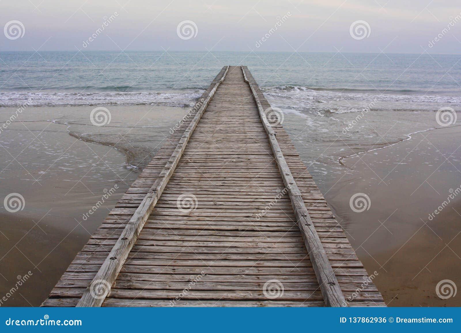 Lång trästrandpromenad på stranden