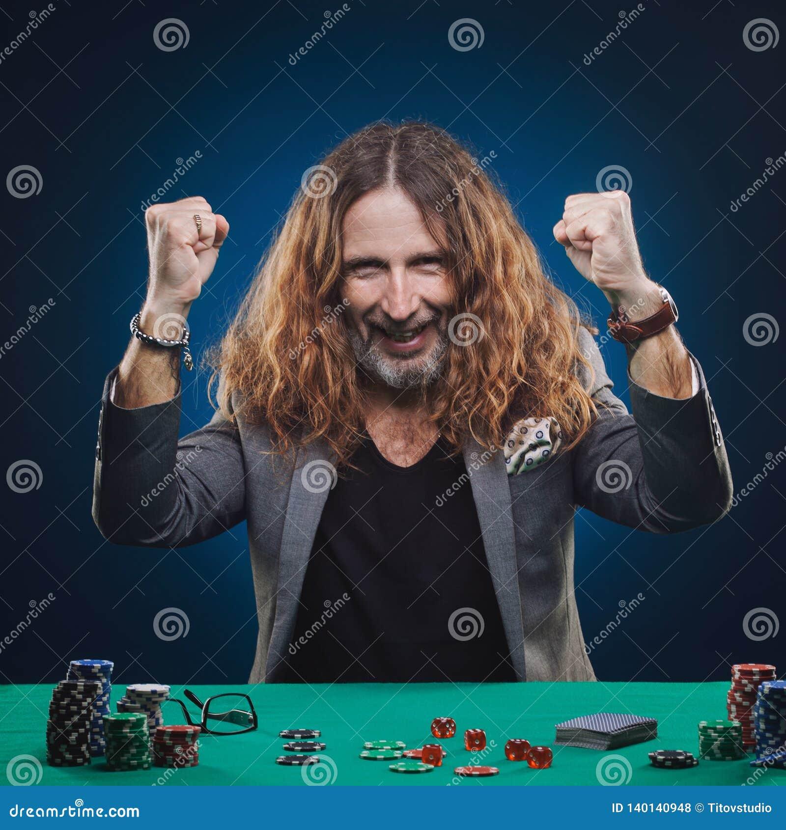 Långhårig stilig man som spelar poker i en kasino