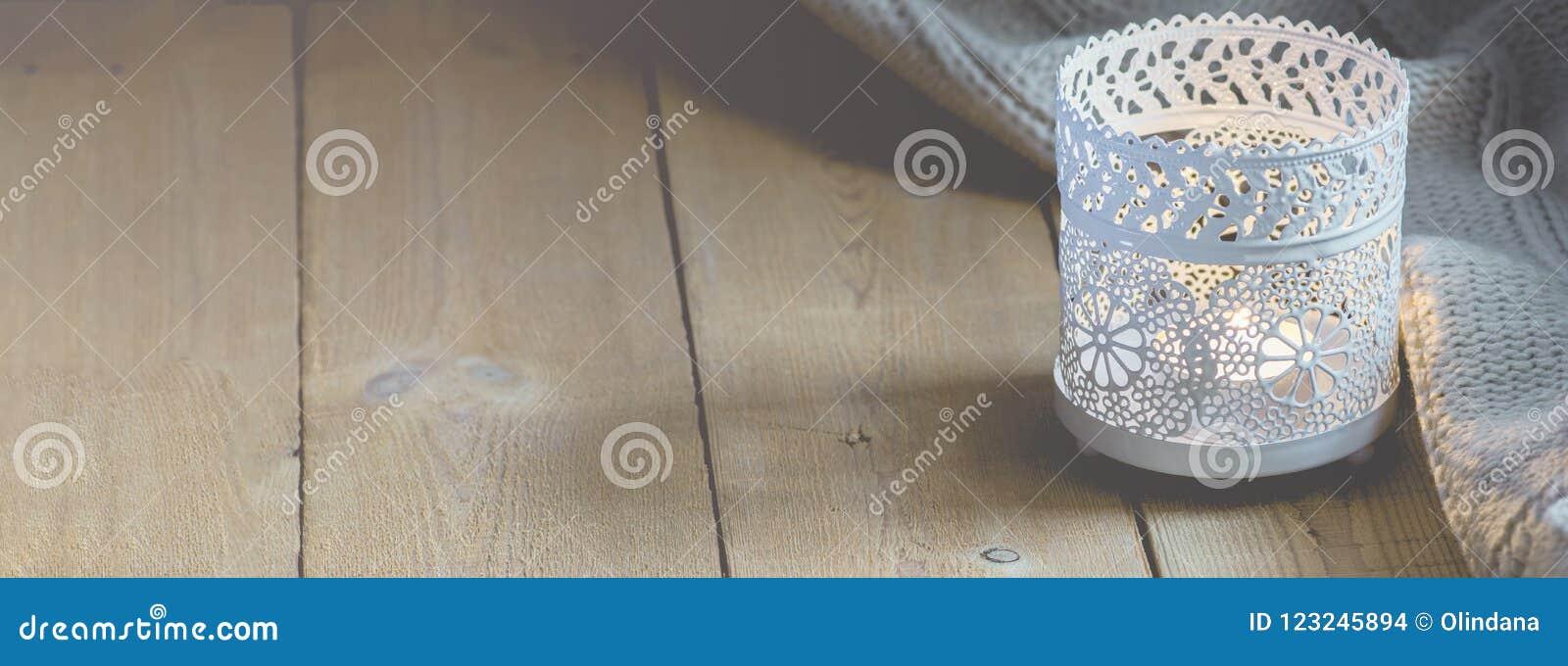 Långt baner för tröja för stearinljus för hemmiljöWebsitesLit stucken vit på den Wood tabellen för planka vid fönstret Hemtrevlig