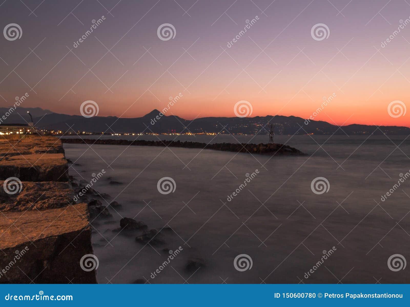 Långt exponeringsfoto av den gamla observatoriet för heraklion kust på kanten av havssolnedgångfärgerna som bakgrund