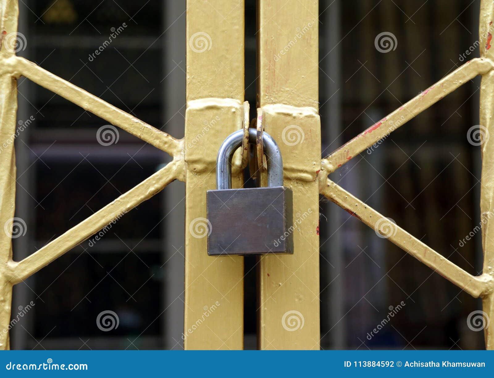 Låset på det guld- metallstaketet, form av staketblicken som X