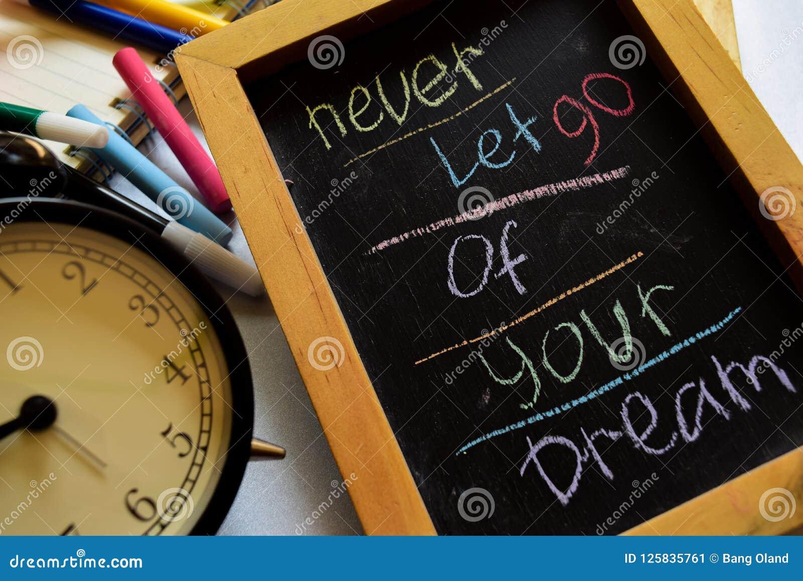 Låt aldrig går av din dröm på färgrikt handskrivet för uttryck på den svart tavlan, ringklockan med motivation och utbildningsbeg