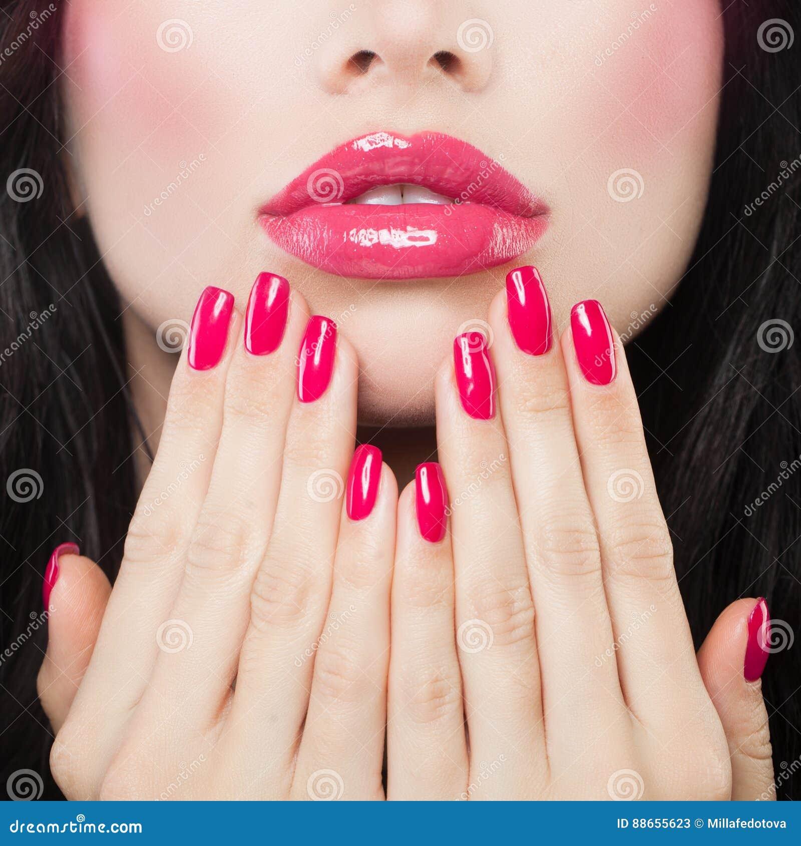 Lèvres de maquillage avec le rouge à lèvres rose, le Lipgloss et la manucure
