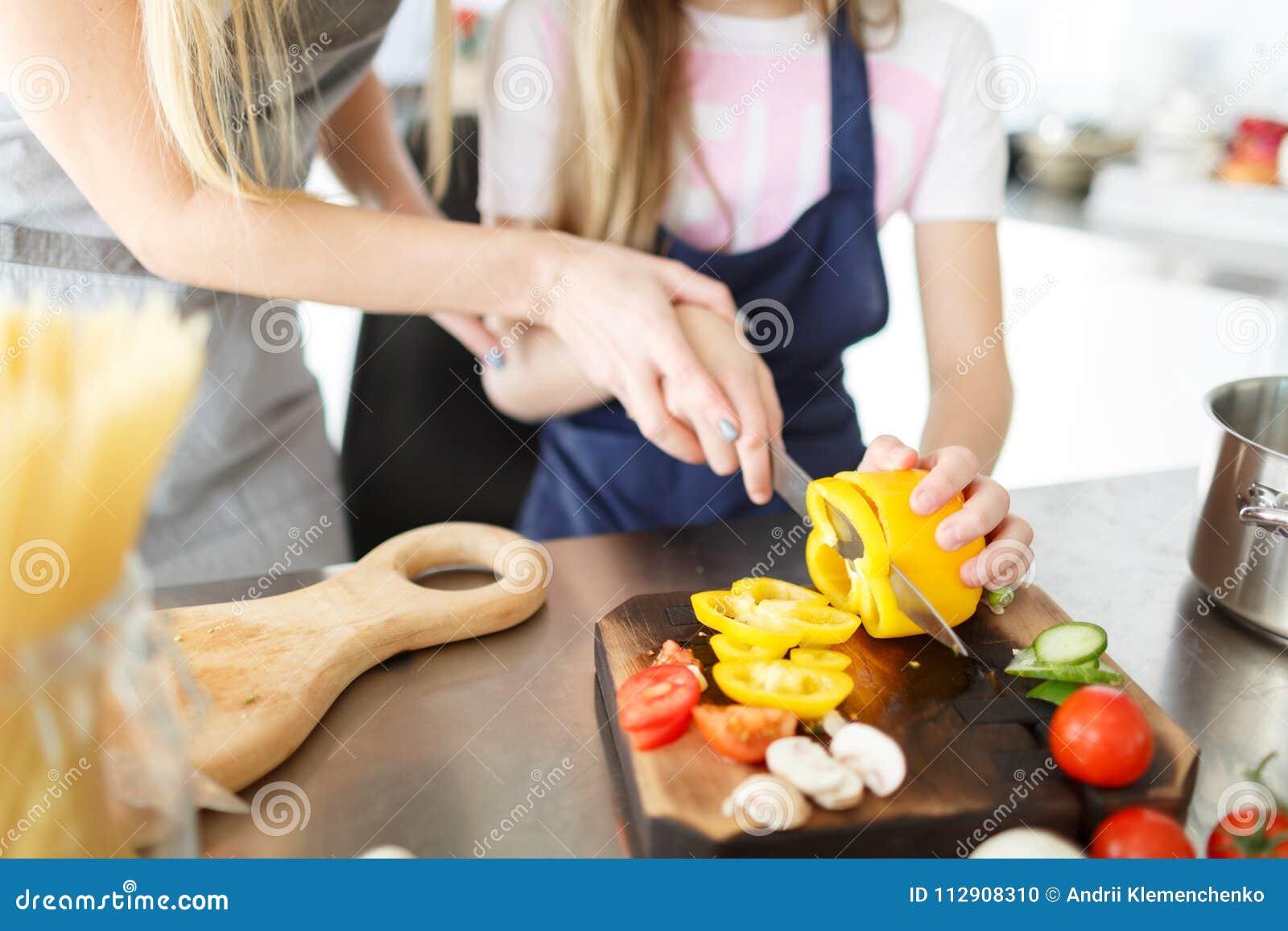 Légumes d une coupe de fille pour la salade sur un bureau en bois