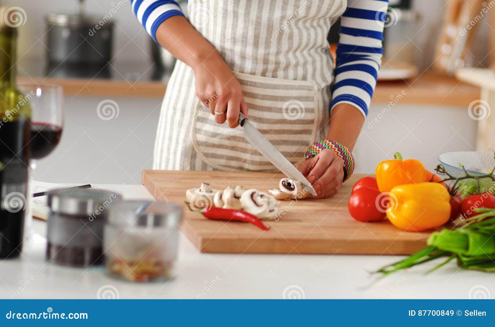 Légumes de découpage de jeune femme dans la cuisine