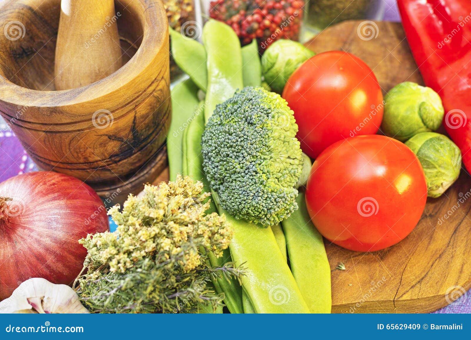 Légumes frais et sains, rouges et verts, brocoli, tomates, oignon sur la planche à découper en bois olive et mortel
