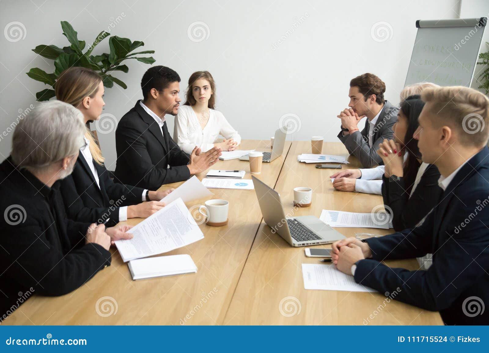 Líder da equipa preto focalizado que fala aos colegas na reunião de grupo