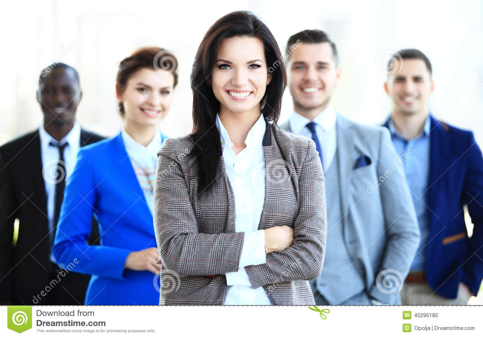 Líder de negócio fêmea novo feliz que está na frente de sua equipe