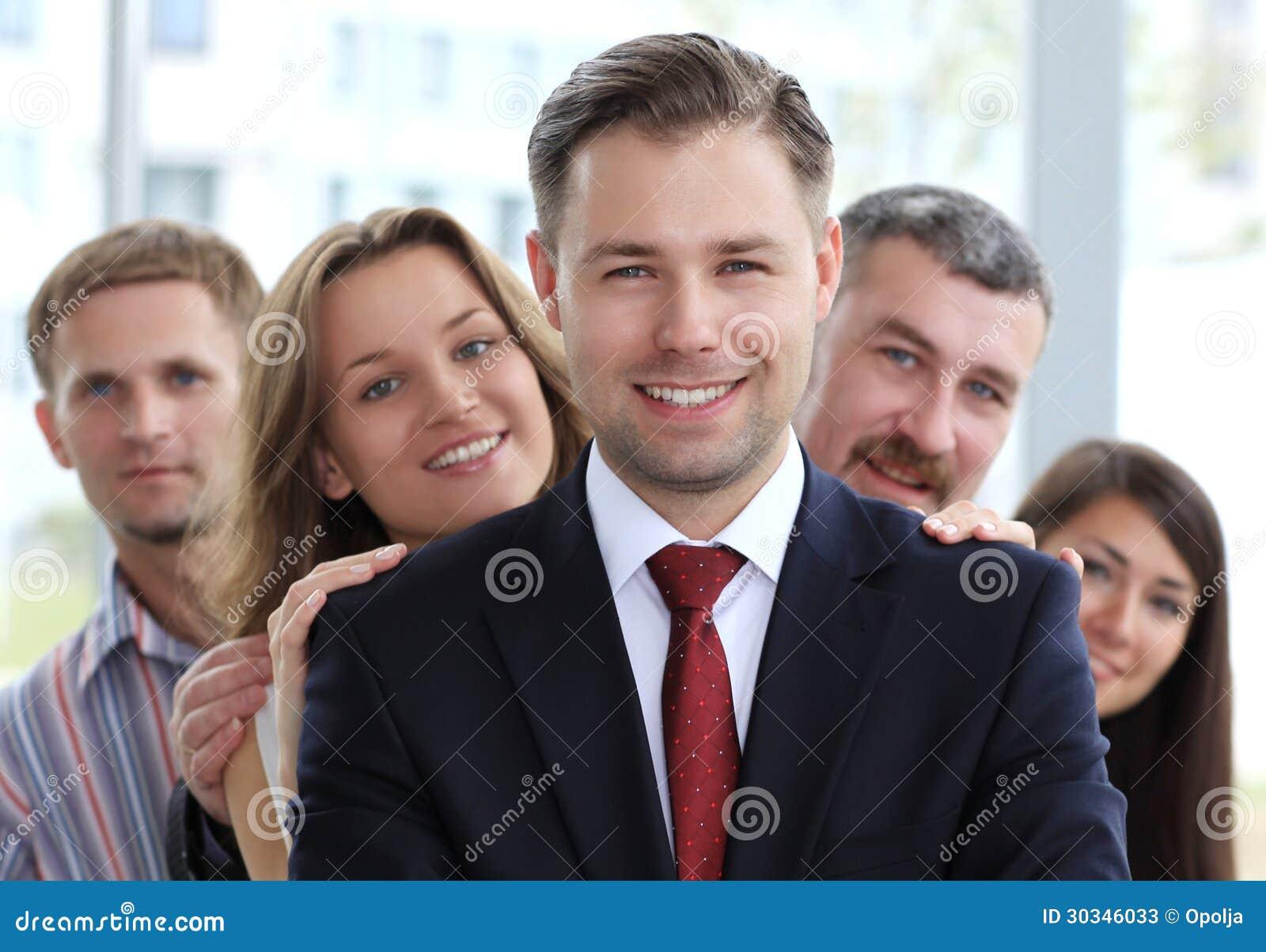 Líder de negócio masculino novo que está na frente de sua equipe