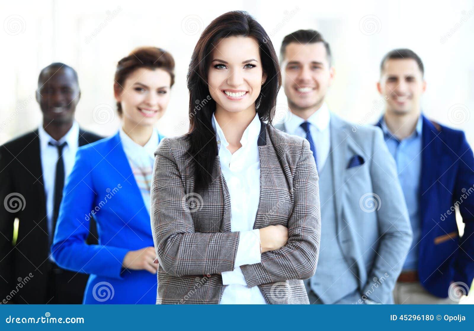 Líder empresarial de sexo femenino joven feliz que se coloca delante de su equipo