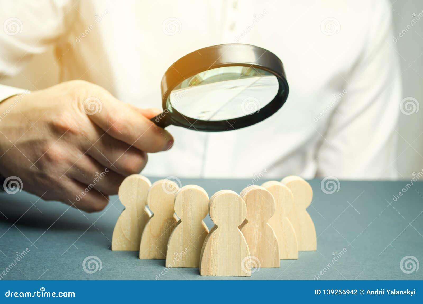 Líder empresarial que sostiene una lupa sobre un equipo de trabajadores El concepto de encontrar a nuevos empleados Teamliding Eq