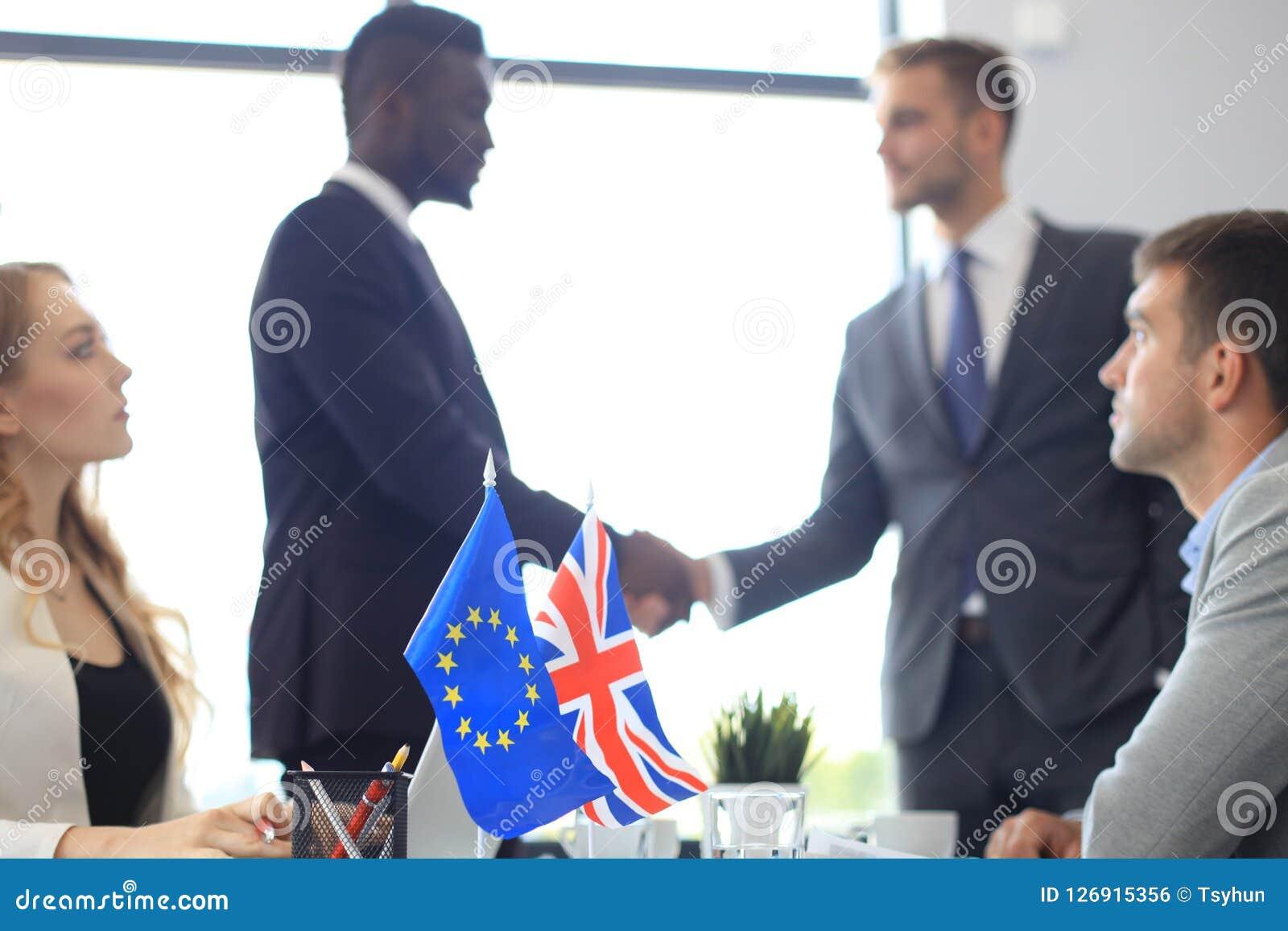 Líderes da União Europeia e do Reino Unido que agitam as mãos em um acordo do negócio Brexit