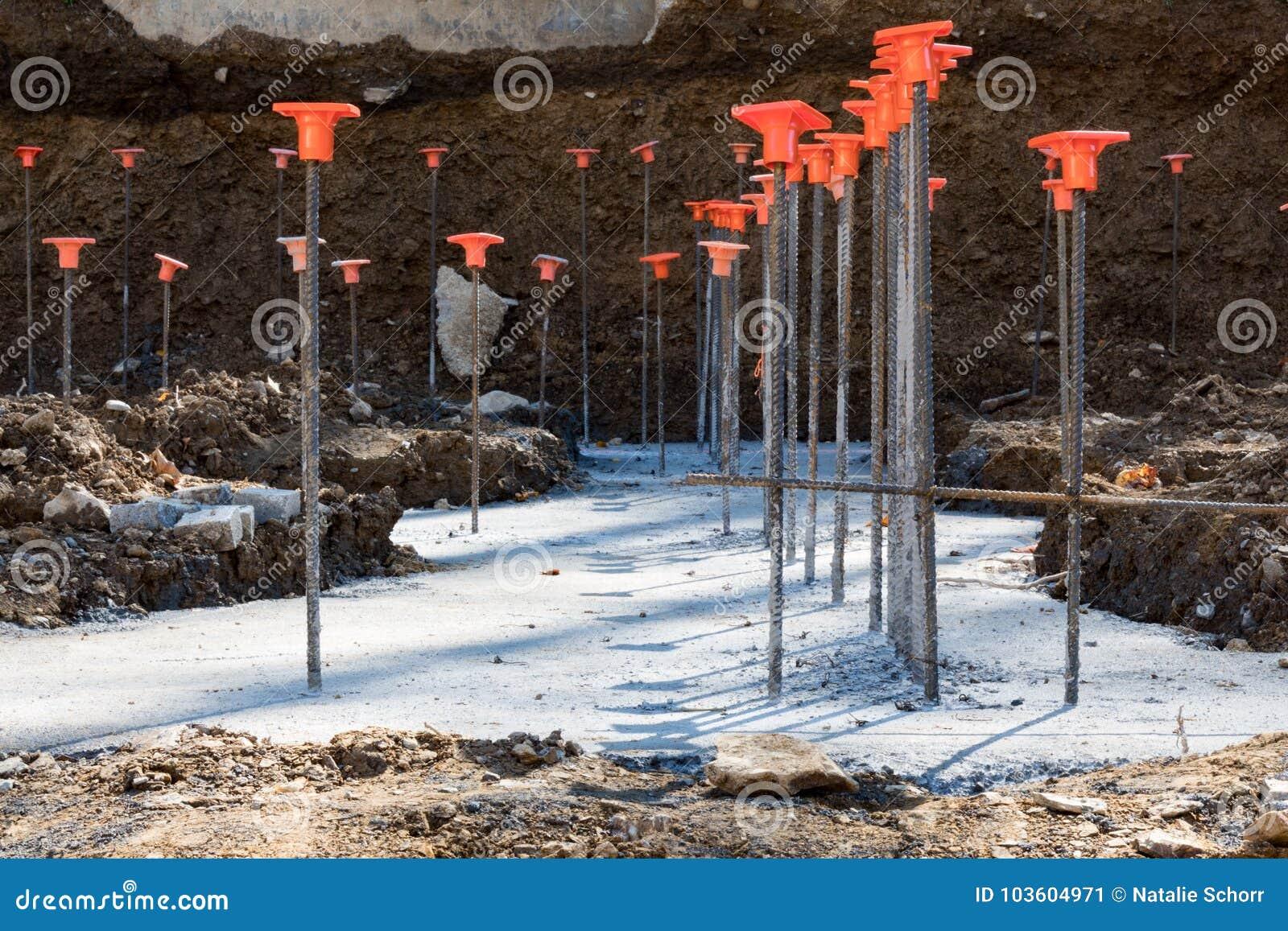 Línea de barras de acero del rebar en pies concretos vertidos