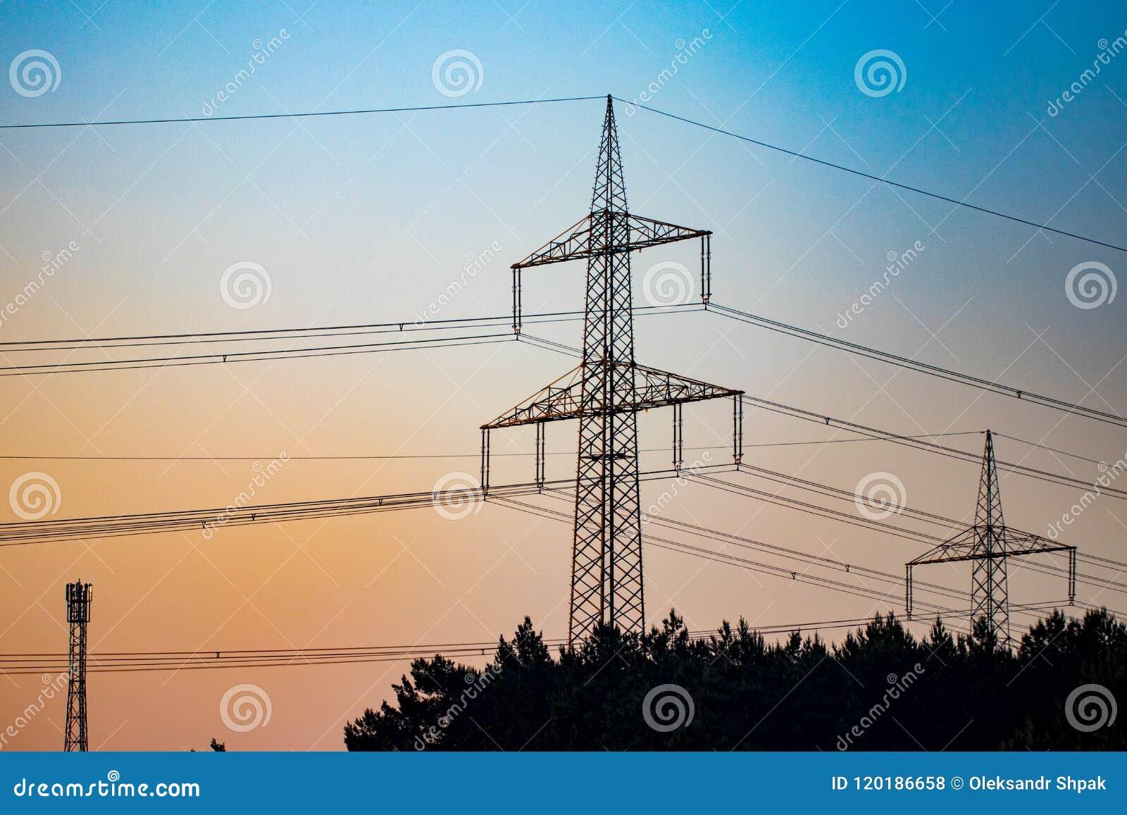 Línea eléctrica del pilón y de la transmisión en puesta del sol