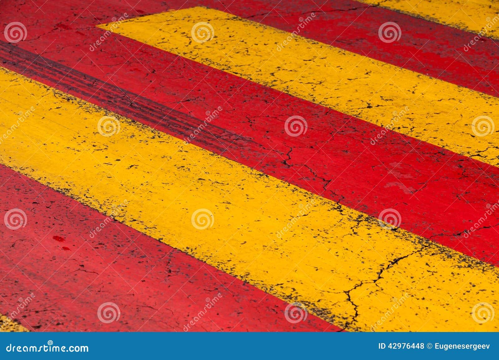 Líneas de la marca de camino del paso de peatones, amarillas y rojas