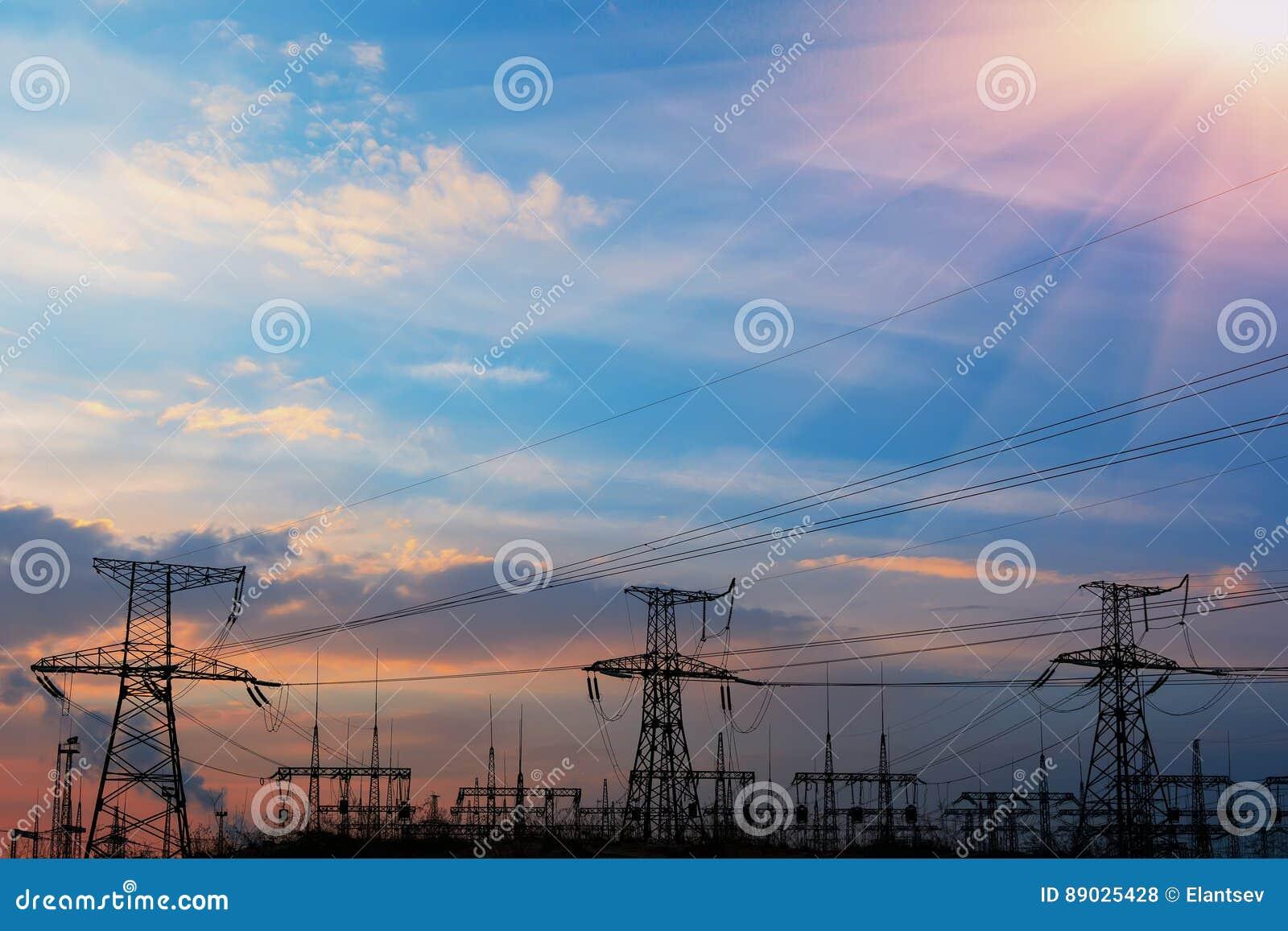 Líneas eléctricas de alto voltaje en la puesta del sol Estación de la distribución de la electricidad Torre eléctrica de alto vol