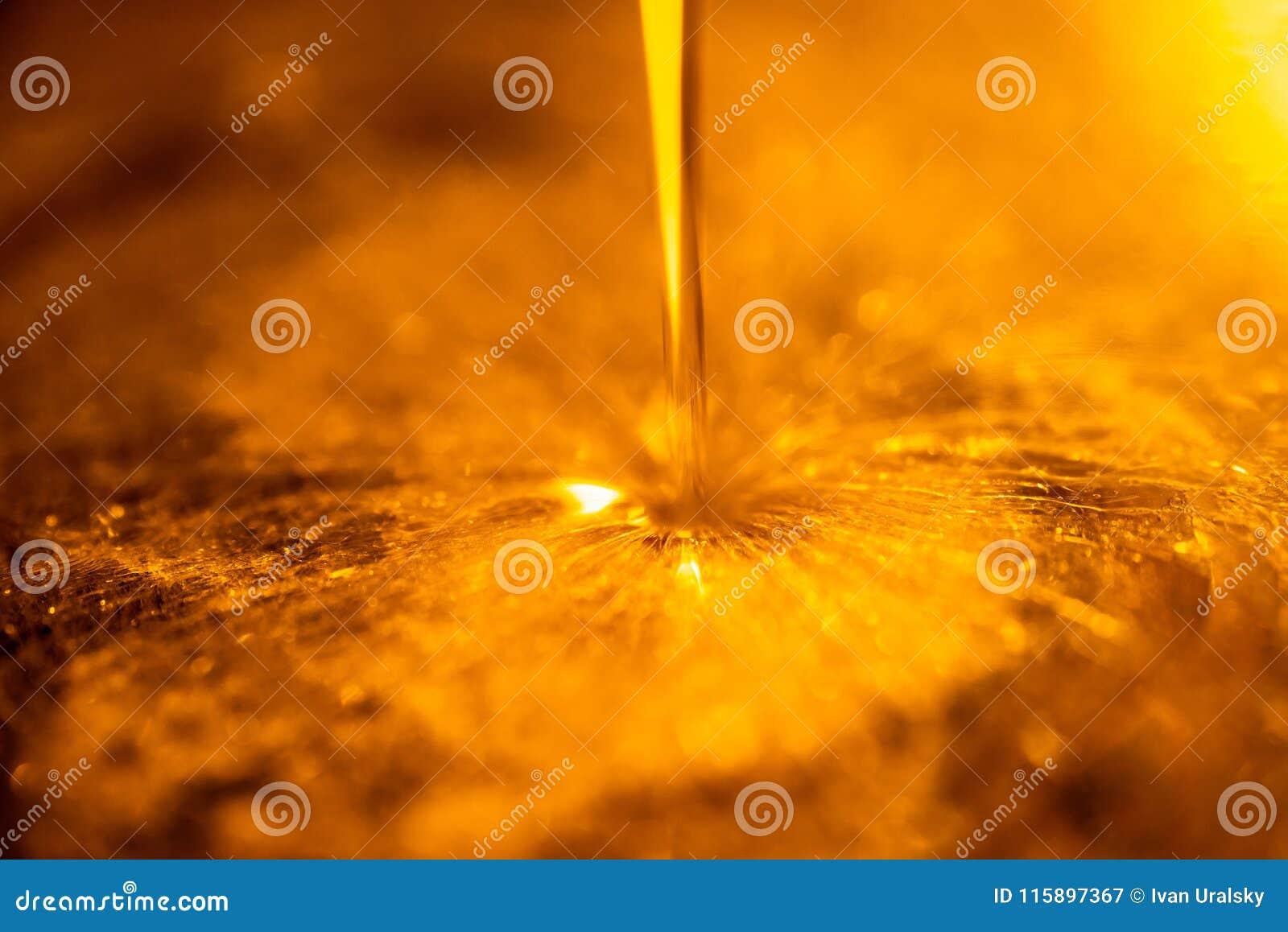 Líquido alaranjado e córrego viscoso do óleo de motor da motocicleta como um fluxo do close-up do mel