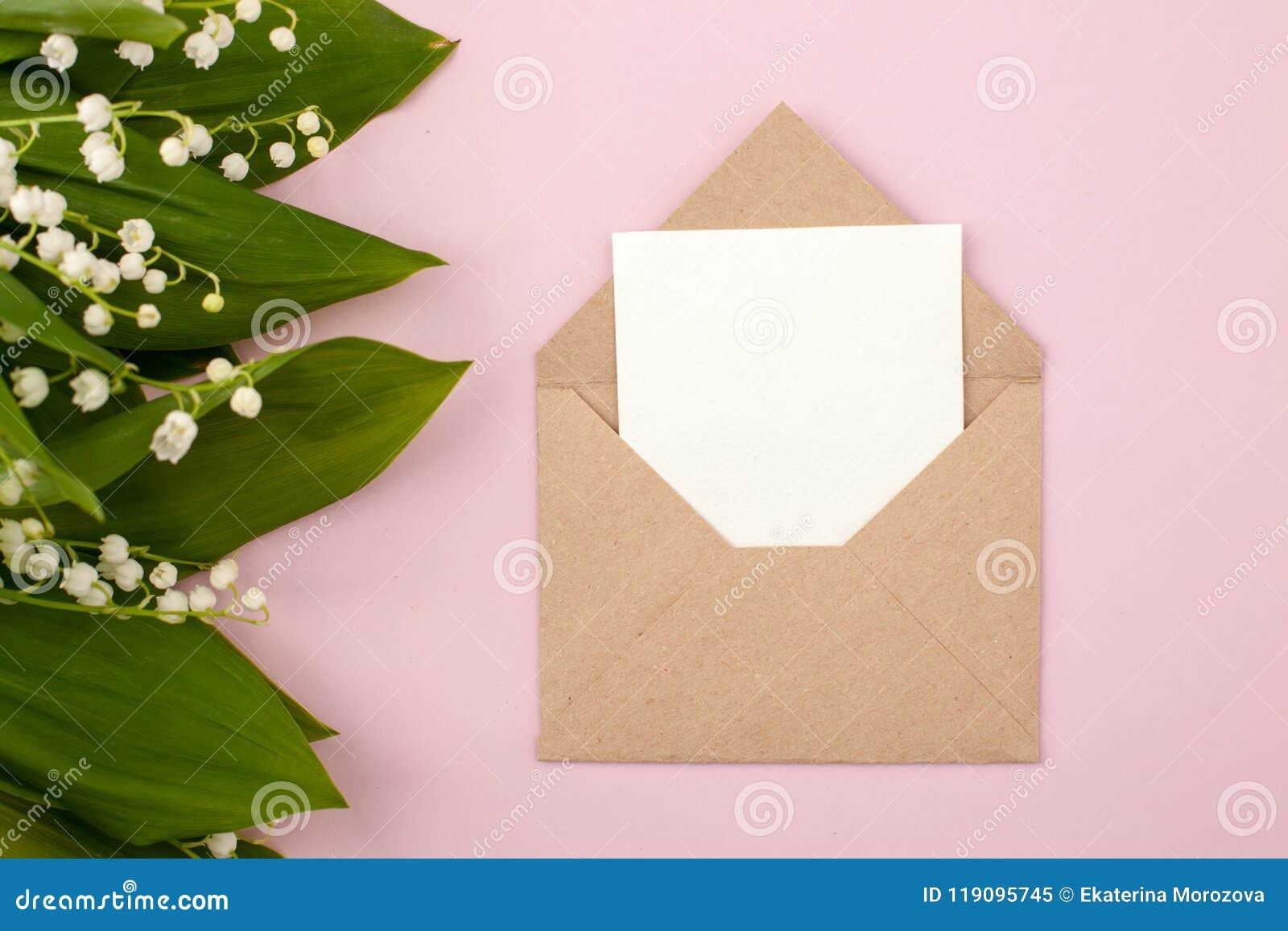 Lírio festivo da flor da composição e do convite do vale no envelope do ofício no fundo do rosa pastel Vista aérea, bouqu