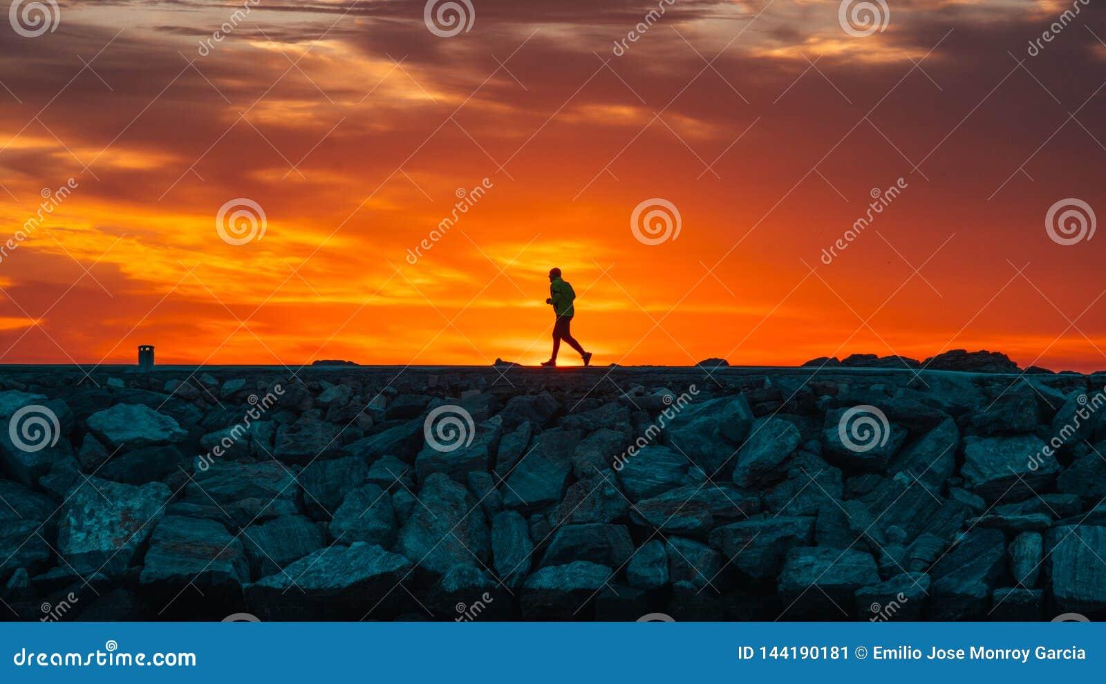 Löpare på soluppgång med solen som skapar konturn