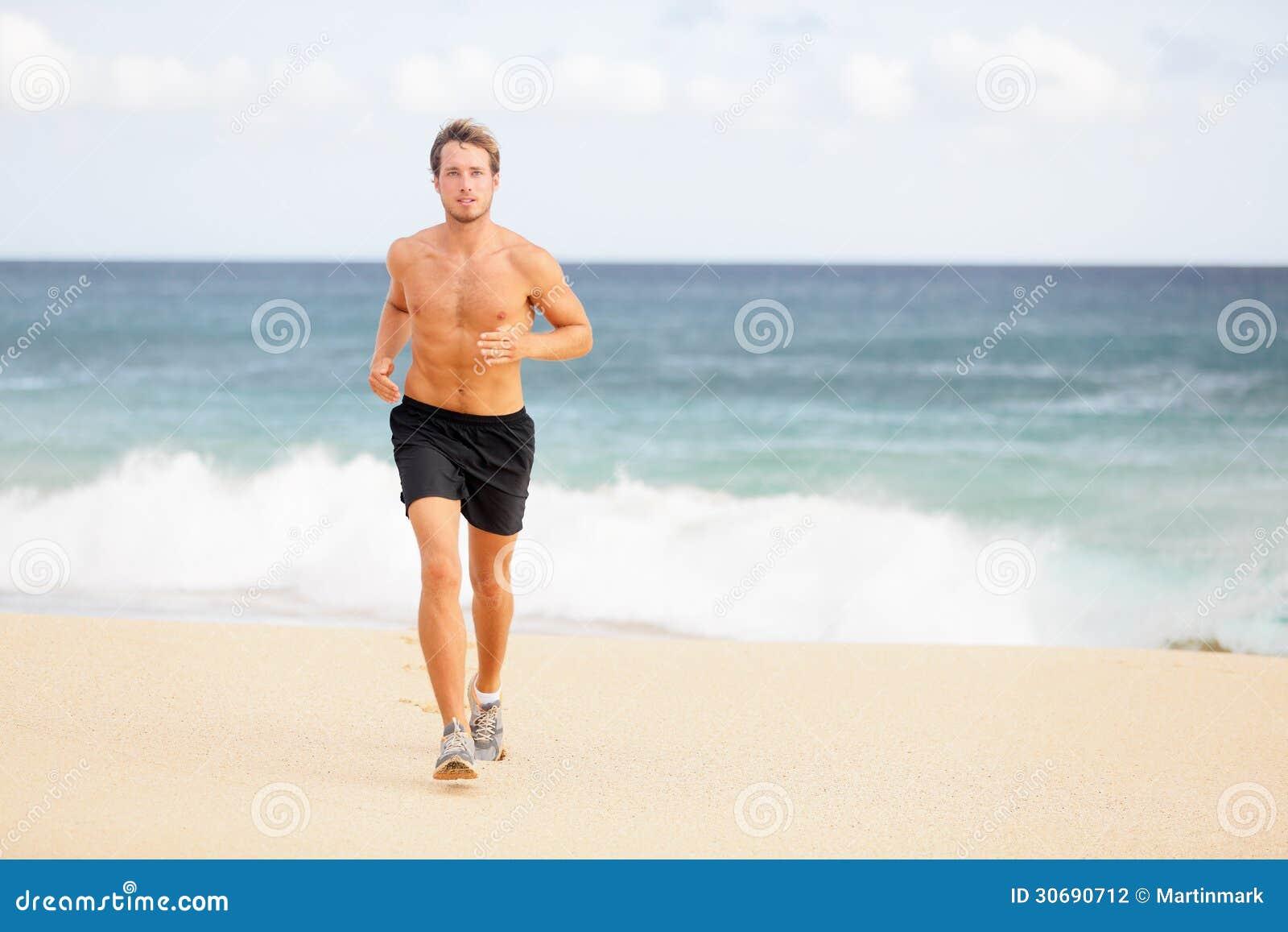 Löpare - ung man som joggar på stranden