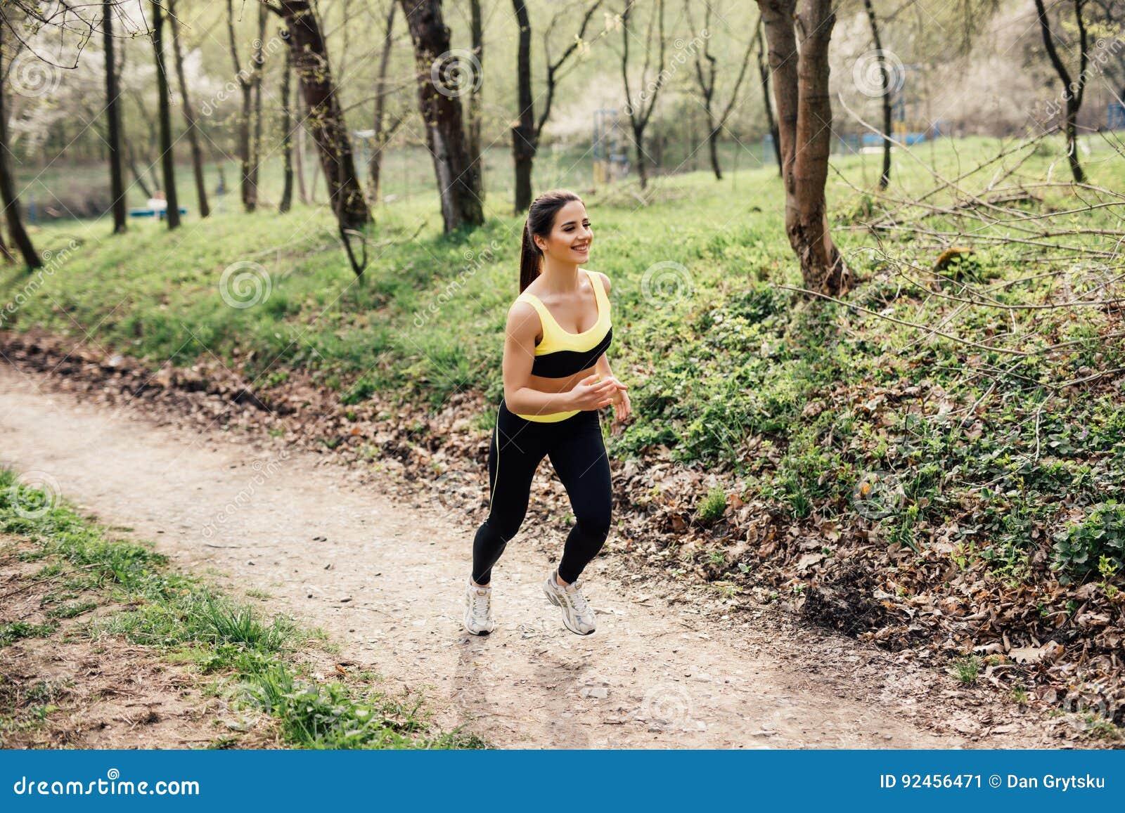 Löpareidrottsman nenspring på tropiskt parkerar begrepp för wellness för genomkörare för kvinnakondition jogga