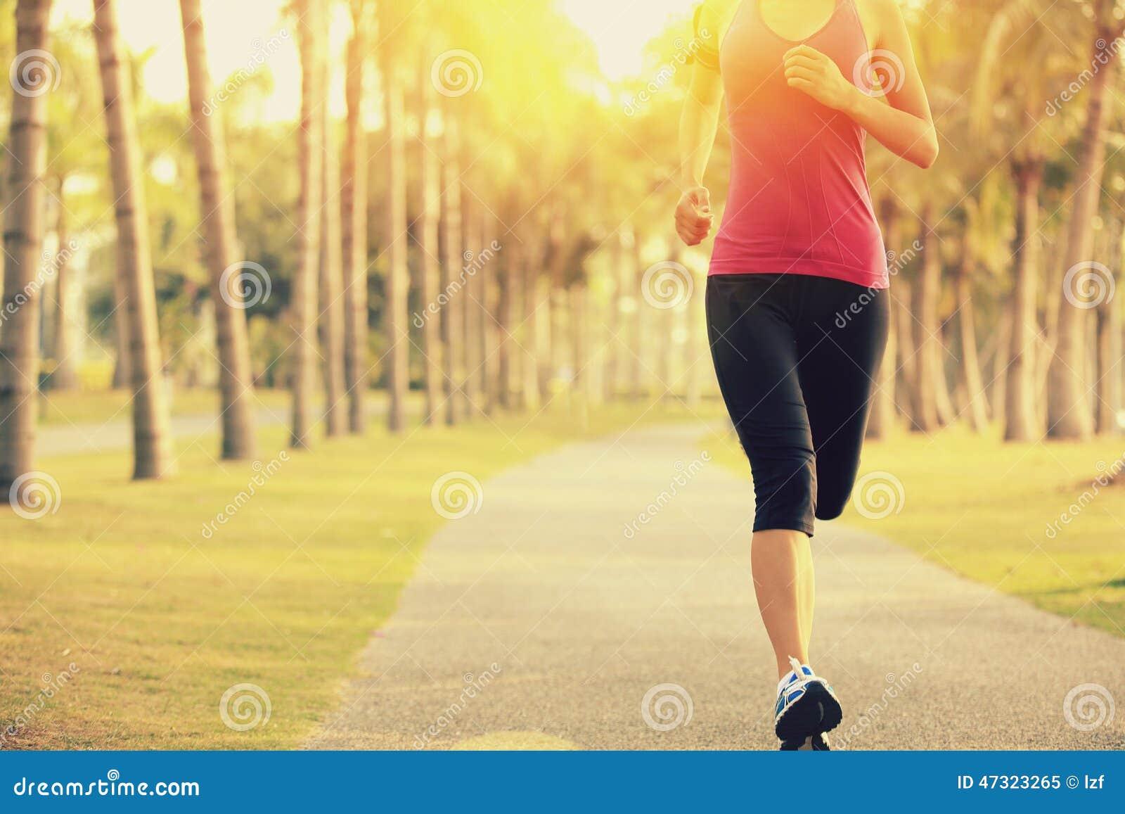 Löpareidrottsman nenspring på tropiskt parkerar jogga genomkörare för kvinnakonditionsoluppgång