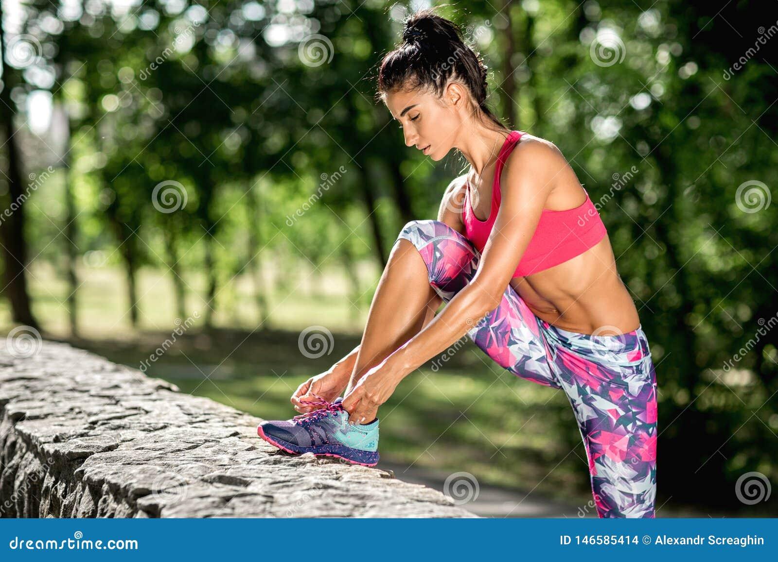 Löparen för den unga kvinnan som binder skosnöre för genomkörare i, parkerar H?rlig passformflicka isolerad kvinna f?r white f?r